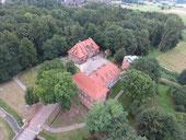 Das Burggelände mit Burggraben, Brücke, Haupthaus, Ziegelsteinturm, Back- und Brauhaus