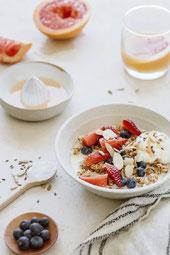 un bol avec des fruits et des cereales, des myrtilles et un jus d'orange