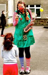 Clownin Lotte mit Saxophon und Spritzkamera mit Mädchen in Flüchltingsheim