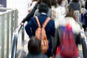 画像;駅エスカレーターに乗る人たち