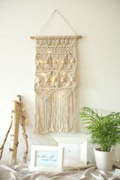 Macramee - Wandbehang mit Microlichterkette geschmückt und mit Grünpflanze und Bilderrahmen auf Sideboard arrangiert.