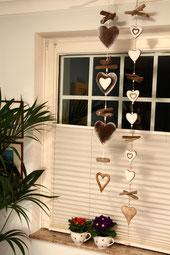Zwei Girlanden aus braunen und weißen Holzherzen am Fenster aufgehängt