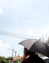 道路では暑さを避けるため、日傘を差して歩く人の姿も=26日