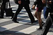 画像;横断歩道を渡る会社員の足元