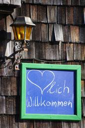 """""""Herzlich Willkommen"""" (der Herz in """"Herzlich"""" als Herz gemalt), mit Kreide auf blauer Tafel mit grünem Rahmen auf einer Wand mit Holzschindeln angebracht, daneben eine alte Laterne"""