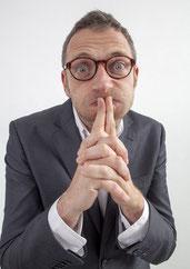 Mittelständischer Unternehmer im Anzug, zweifelnd und ratlos.