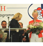 Auf der Bühne: links Markus Genz.- Helga Karl überreicht Senatorin Knake-Werner einen Blumenstrauss. Foto: (c) Helga Karl