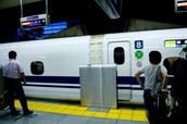 画像;ホームに到着した新幹線とビジネスマン