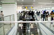 画像;駅エスカレーターでホームへ向かう人々