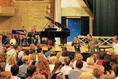 Dozent Hubert Minkenberg (2. v. re.) führt die zahlreichen Sänger und Sängerinnen in der Aula zu einem großen Chor zusammen. Den intensiven Proben in der Aula folgte ein Abschlusskonzert. Foto: Uwe Heldens