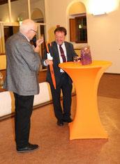 """Michael Brockerhoff überreicht dem Referenten als kleines Dankeschön """"himmlische"""" Pralinen und einen Schirm der Bürgerstiftung Gerricus."""