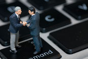 画像:パソコンの上で握手するビジネスマン人形