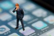 画像;スマートフォンに上にビジネスマンの人形