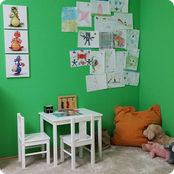 Kinderecke des Behandlungszimmers mit Zeichnungen auf grüner Wand