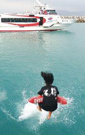 大好きな先生が島を離れる。子どもたちは船に向かって飛び込んだ=3月31日午後、竹富港