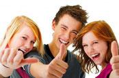 trois visages jeunes très souriants montrant avec leurs pouces que ce lieu est formidable