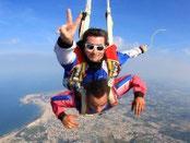 deux personnes sautent en tandem en parachute