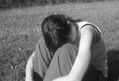 Frau auf Wiese mit Kopf auf Knien, traurig, erschöpft