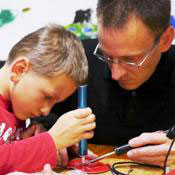 Junge lötet an einem tinobo Roboterbausatz