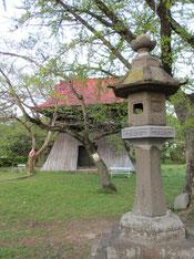 赤い屋根の鐘楼と石灯籠