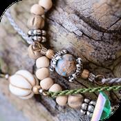 Bijoux micro macramé avec beaucoup de perles posés sur une écorce de bois