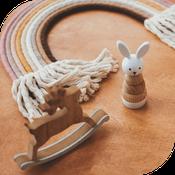macramé arc-en-ciel pastel posé avec deux jouets bois lapin et renne