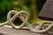 Ein Seil das zu einem Knoten geformt wurde und ein Herz bildet