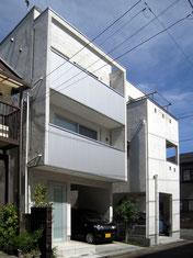 木造3階建て住宅。狭い間口を左官と金属の仕上げで箱型にデザイン。白く清潔感ある外観としている。