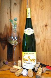 Een fles Elzas Gewurztraminer in een kist met een glas en kurken
