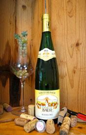 Een fles Elzas Riesling wijn in een kist met een opener
