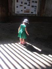 コントラストの強い光の中入る娘。自分のスカートのレースを通過する光に気づき、遊んでいる。