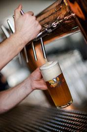 Hand zapt natürtrübes Bier in Pilsglas an Zapfanlage