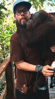 Geschockter Mann mit Kappe hat Orang Utan auf dem Arm