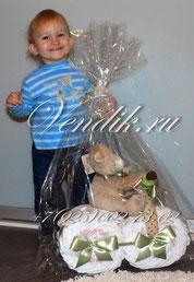 Счастливый малыш с подарком - мотоциклом из памперсов