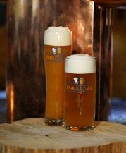 Weizenbierglas steht neben Pilsglas mit Bier auf Holzscheibe