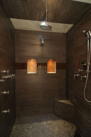 Dark brown shower with large tiles and glass accents.