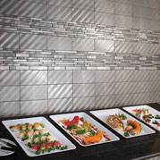 Silver metallic tiles on a wall behind a colorful spread of sushi.