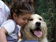 Una bambina e un golden retriver durante una seduta di Pet Therapy