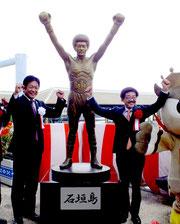 等身大の具志堅用高さんの銅像の横でこぶしを上げる具志堅さん(右)と中山義隆石垣市長=26日午前、離島ターミナル