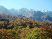 初雪の山々と盛りを迎えた紅葉