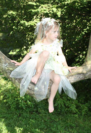 Ein Mädchen in einem Blumenkleid sitz in einem Baum vielleicht ist es auch eine kleine Fee oder Elfe mit Blumen und Bändern im Haar