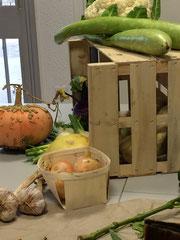 Une composition de nos légumes du marché avec cagette, oignons et courges serpents