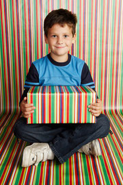 Young boy sitting crosslegged with a gift wrapped box on his knees