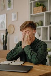 Ein rotblonder, weisser, junger Mann hält sich mit den Handinnenflächen die Augen zu und sitz an einem Schreibtisch mit einem Laptop. Der Laptop ist geschlossen. Im Hintergrund sieht man ein Bücherregal und Bilder an der Wand.