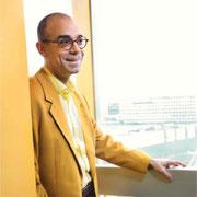 Photo de cet homme souriant, crane rasé portant des lunettes rondes en veston jaune, avec une main posée sur un rebord de fenêtre