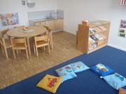 ein Gruppenzimmer mit Spielteppich und Essbereich