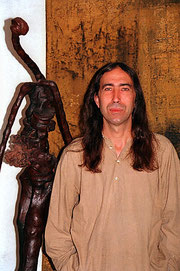 Amador Vallina with a sculpture in front of a painting