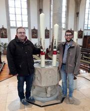 Foto: Johannes Leushacke (l.) und Martin Reuter (r.) präsentieren die Osterkerzen vor dem Taufstein in St. Vitus