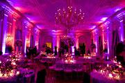 DJ plus Lichttechnik und Ambiente Licht in einem großen Saal. Lichtszenerie ist Lila und Rot