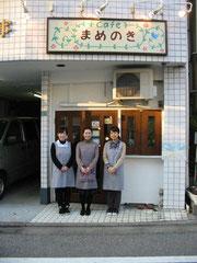「カフェまめのき」の前でスタッフたち。左から佐藤舞優さん、清水沙恵さん 安田みゆきさん